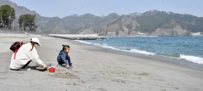 一般開放が始まった根浜海岸で砂遊びする親子