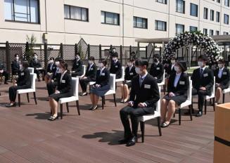 屋外の会場で入社式に臨む花巻温泉の新入社員=1日、花巻市湯本