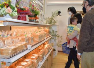 オープンしたばかりのパン屋で商品を選ぶ買い物客