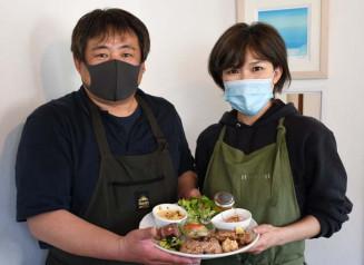 「おまかせ酵素玄米プレート」を手に来店を期待する小林延行さん、恵美さん夫妻