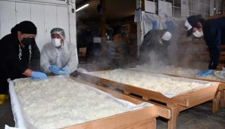 湯気が立ちこめる蔵で、蒸し上がった米の感触を確かめる久慈浩介社長(左)ら