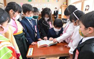 入学式で贈られた辞書を興味津々の様子でめくる豊間根小の新1年生