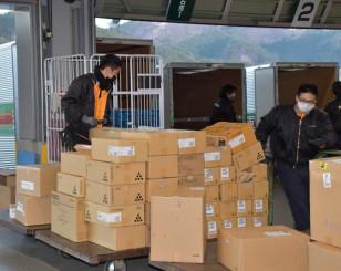 荷物を整理する福山通運釜石営業所の従業員。三陸道釜石北IC近くの立地を生かしている=釜石市片岸町
