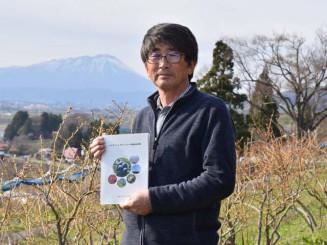 記念誌を手にブルーベリーの木の前で今後の飛躍を誓う松本正勝事務局長
