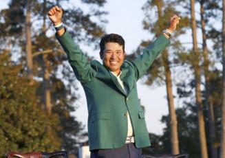 米ゴルフのマスターズ・トーナメントで、日本男子初のメジャー制覇を果たし、グリーンジャケットを着て両手を上げる松山英樹=11日、米ジョージア州のオーガスタ・ナショナルGC(ロイター=共同)