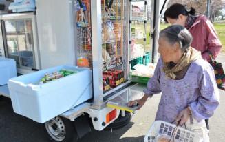 生鮮食品などが並ぶ移動販売車で買い物を楽しむ住民ら