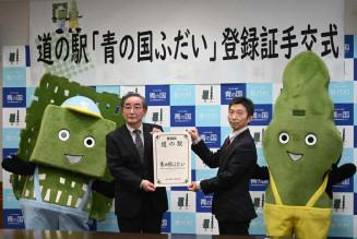 石渡史浩所長(右)から登録証を受け取る柾屋伸夫村長