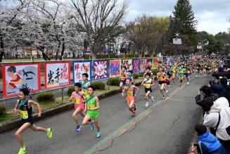 参加中学校の生徒たちがデザインした横断幕に背中を押され、力強く走る中学校男子の選手=18日、盛岡市みたけ・県営運動公園