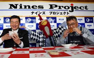 発表会で「オブチキバーガー」を味わう阿部繁之社長(右)と晴山裕康村長。Mrオブチキ(中央)も盛り上げた