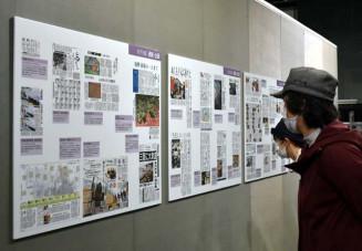 被災地の課題を伝える連載や企画記事に見入る来場者=24日、横浜市・日本新聞博物館