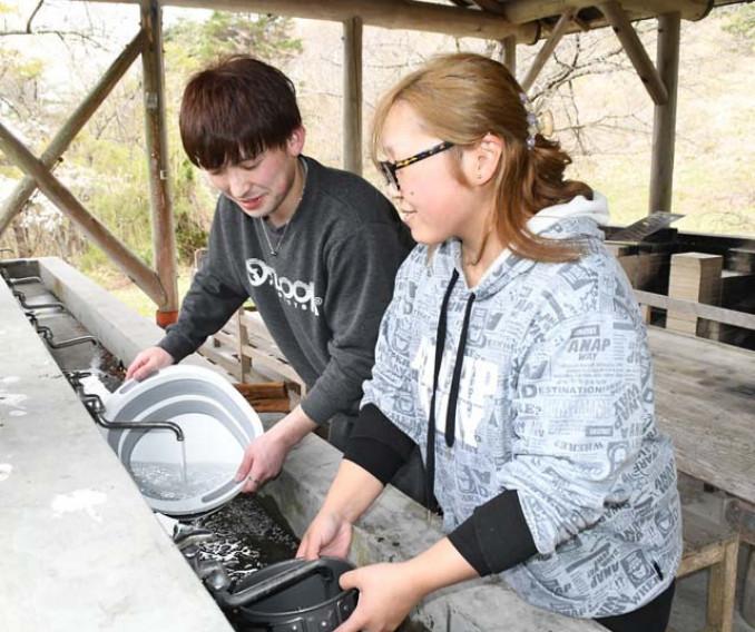 炊事棟で食器を洗う利用者