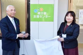 「いわて被災者支援センター」の看板をお披露目する山屋理恵センター長(右)ら=27日、釜石市