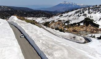 最大9.5メートルの雪の壁が続き、観光客を出迎えている八幡平樹海ライン=27日午後0時55分、八幡平市(本社小型無人機から撮影)