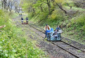 新緑が彩る線路をレールバイクで走る家族連れ=3日、宮古市刈屋