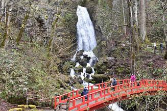 不動の滝の迫力ある眺めを楽しみながら散策する観光客