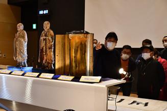 佐々木勝宏さん(左)の解説で、安岡良運作の仏像など展示資料を見る来場者