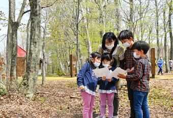 森の中を散策して隠された文字を探す子どもたち
