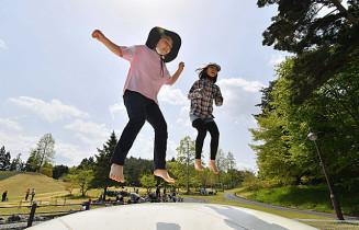 青空の下、跳躍器具で遊ぶ子どもたち=4日、奥州市水沢・市ふれあいの丘公園