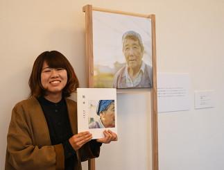 写真集「報せ」を手にする飯塚麻美さん