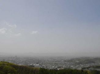 黄砂とみられる影響で、地表付近が白くかすんだ盛岡市中心部=8日午後1時20分、同市新庄・岩山展望台