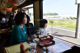 瓶ドンやにぎりずしを食べながら車窓の風景を楽しむ乗客