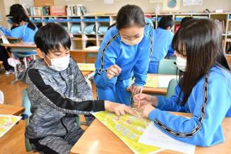 松尾鉱山があった「緑ガ丘地区」の絵図と、当時の写真を見比べる児童