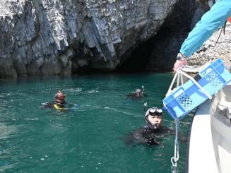 「青の洞窟」として知られる八戸穴の入り口付近で、海底にワインを運ぶ堀内繁喜さん(左から3人目)と仲間のダイバーら