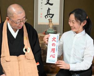 火の用心の標語ステッカーを手に、祖父の目時大堂さんから大火当時の話を聞く桜さん(右)