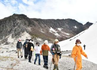 残雪が残る中、雄大な自然を楽しみながら歩みを進める登山者