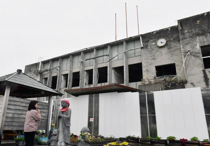 解体工事を目前に控える旧役場庁舎前で手を合わせる藤原マチ子さん=11日、大槌町新町