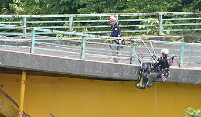 意識不明の救助者を想定し、迅速に引き上げる救助方法を披露する日本空糸の伊藤徳光代表(右)ら