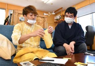 漆染めの生地を見てお守り作りの構想を練る小保内威彦宮司(右)と小軽米健太代表取締役