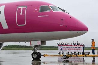 名古屋線の就航10年を迎え、横断幕を掲げて乗客を見送る関係者=花巻市・花巻空港