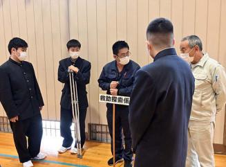 避難訓練後に、災害時の役割について教師と確認する久慈工高の生徒