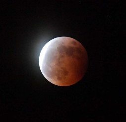太陽からかすかに届く光に照らされ、赤銅色となって浮かぶ月=26日午後8時41分、二戸市石切所・馬仙峡展望台(報道部・桜岡流星撮影)