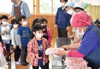 おおぶけキッズカフェの手作り弁当を受け取る児童