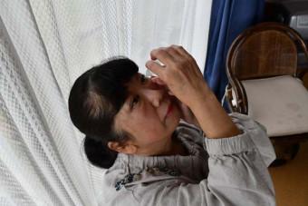 眼瞼下垂の緩和効果がある目薬を差す小野寺ひろ子さん。1日に何度も使い、仕事中も常備する