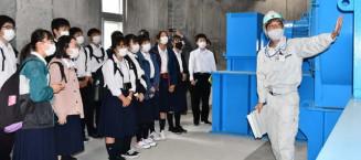 操作室内で水門開閉のシステムについて学ぶ生徒ら