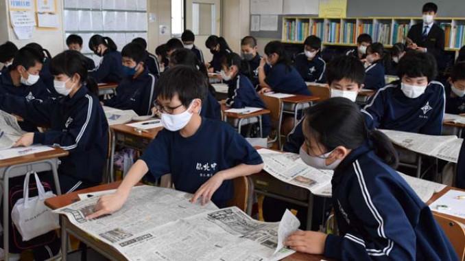 新聞紙面を開き、興味のある記事を探す仙北中の生徒ら