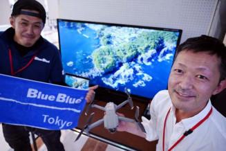 ドローンで大船渡市を撮影した「僕らの街を空から観たら」展を開いている吉田剛さん(右)