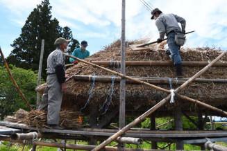 佐藤才治さん(左)の指示に従い、あずまやのカヤの形を整える研修生