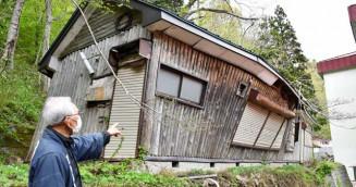 雪の重みで大きく傾いた木造小屋。解体の見通しは立っていない