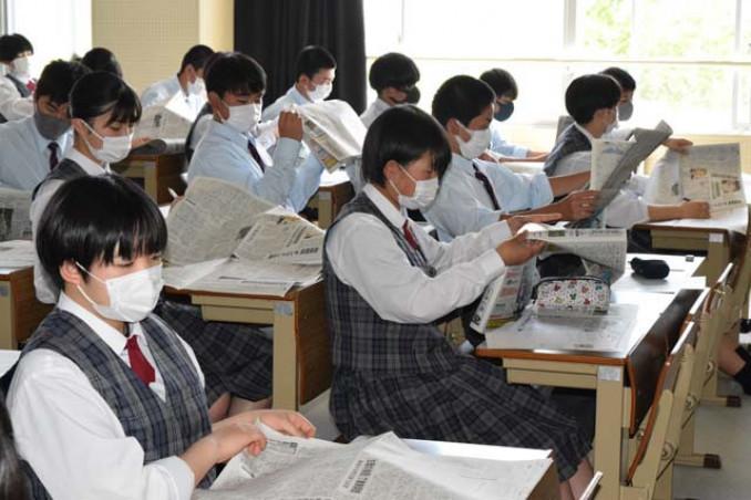 新聞を広げ、紙面構成について学ぶ花巻南高の生徒