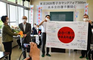 応援の寄せ書きを広げて見せる水本選手の父淳一さん(右から2人目)と、花束を受け取る母久美さん(左)