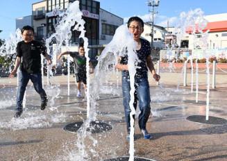 久慈駅前いつくし広場の噴水を浴びて涼む子どもたち=6日、久慈市中央