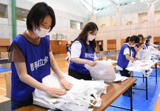 県内の聖火リレーで使用される備品を仕分ける県立大の学生ボランティア=10日、滝沢市巣子
