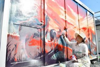 壁に絵を描くAyamiさん。廃材を絵の具にしようと全国を巡る