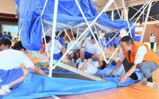 損壊した建物から人命を救助する場面を想定した訓練に取り組む生徒と千葉稔会長(右)