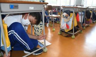 地震を想定し机の下で身を守る厳美小の6年生