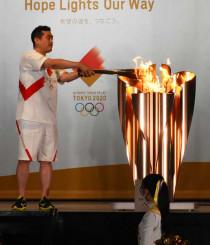 本県初日のリレーを終え、聖火皿に火をともす二十山仁さん=16日、久慈市・アンバーホール